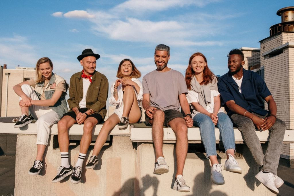 A group of people sitting on concrete on a building rooftop.