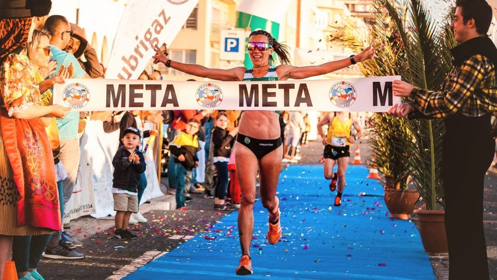 Photo of a woman reaching the finish line of a marathon.