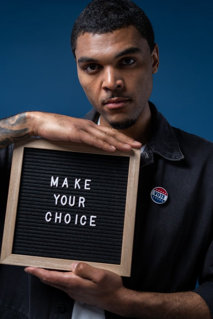 A man holding a writing in a wooden frame that says 'make your choice'